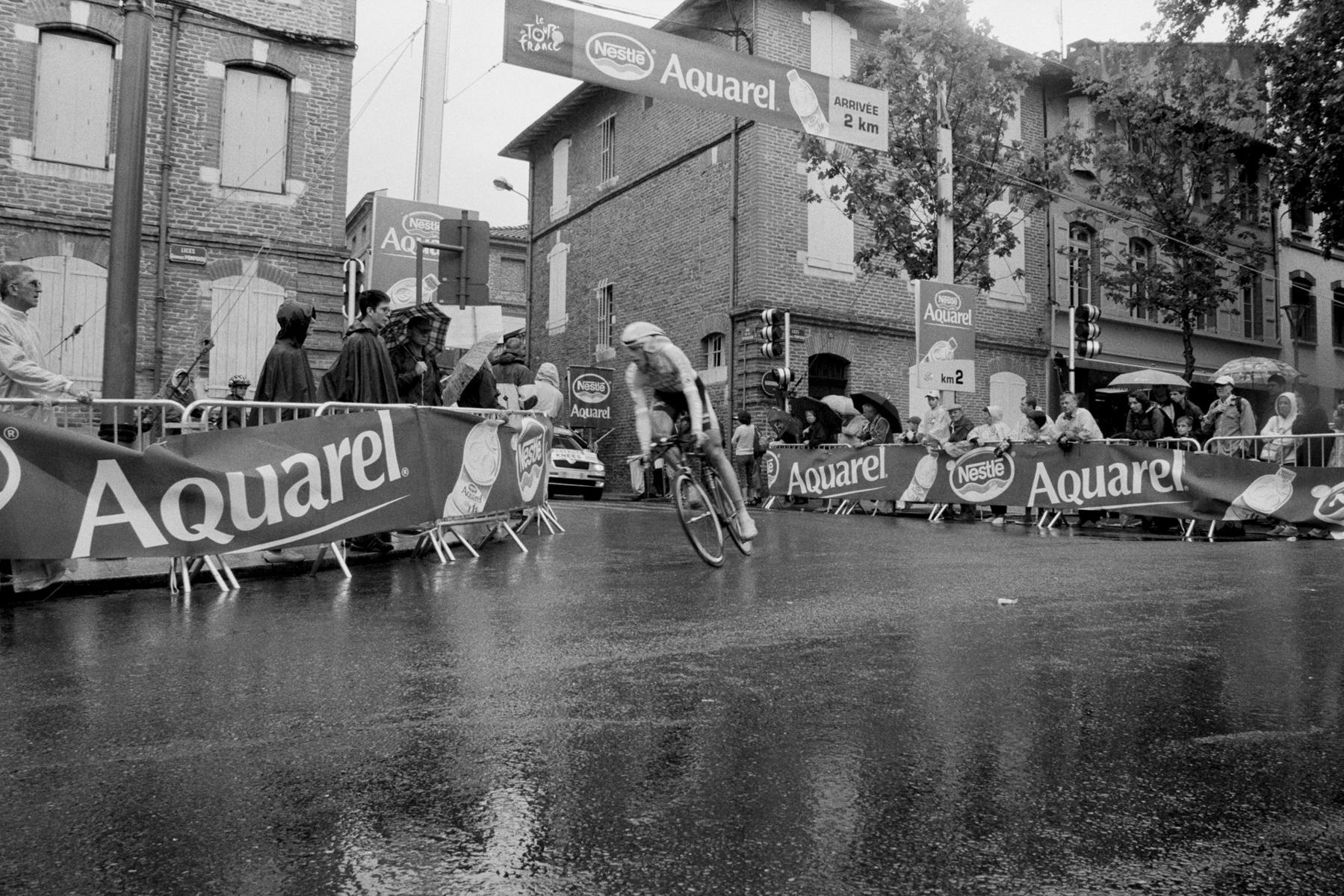 Le Tour de France 2007 When it rains the cyclists have to slow down before the curve - enabling the fans a closer look. Quand il pleut, les coureurs doivent ralentir avant d'aborder les virages, les spectateurs n'en ont que plus de temps pour apprécier leurs favoris. Bei Regen müssen die Fahrer vor der Kurve stark abbremsen – was dem Fan einen genaueren Blick ermöglicht. Cuando llueve los deportistas tienen que frenar antes de la curva, lo cual permite a los admiradores una mirada más cercana.