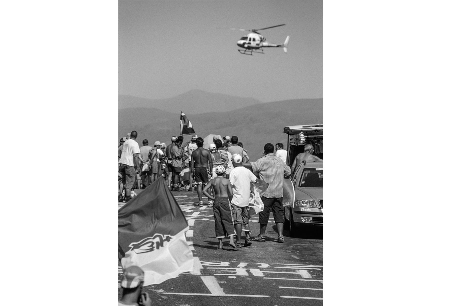 Tour de France 2005, The helicopter announces the approach of the peloton to on-looking fans. Tout le monde le sait, lorsque l'hélicoptère se présente, le peloton ne peut plus être bien loin. Jeder hier weiß: Wenn ein Helikopter erscheint, ist das 'Peloton' nicht mehr weit. Todo el mundo lo sabe, cuando aparece el helicóptero, es la señal que el pelotón ya se acerca.