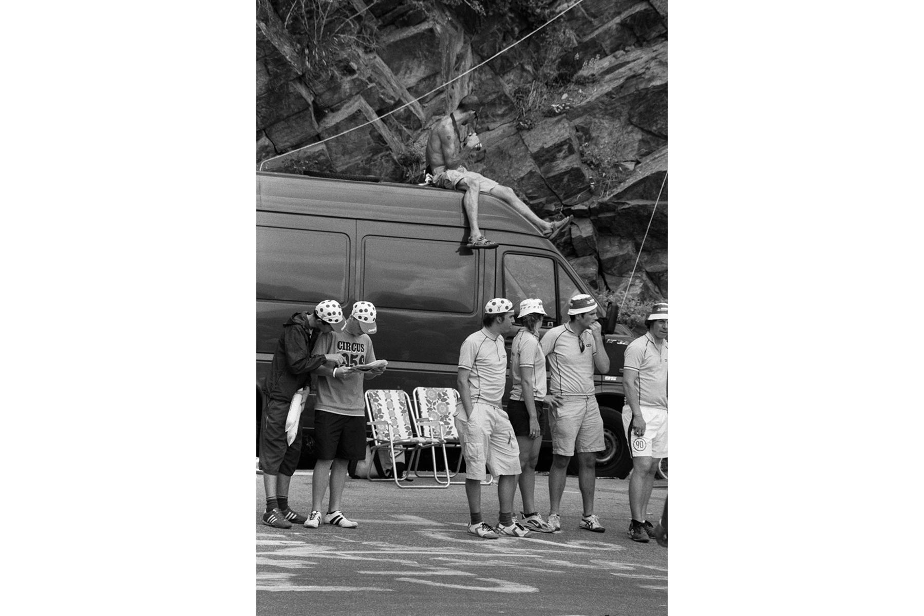 Tour de France 2006 The fans keep busy by studying the listings in the magazines distributed by the official Tour publicity caravan. En attendant les coureurs, les passionnés étudient la liste des cyclistes dans les magazines distribués par la caravane publicitaire. Die Zuschauer warten gespannt. Man studiert die von der Werbekaravane verteilten Magazine. Hier finden sich die Namen aller Fahrer. Los aficionados, mientras esperan, repasan las listas de los participantes en las revistas que distribuye la caravana de publicidad.