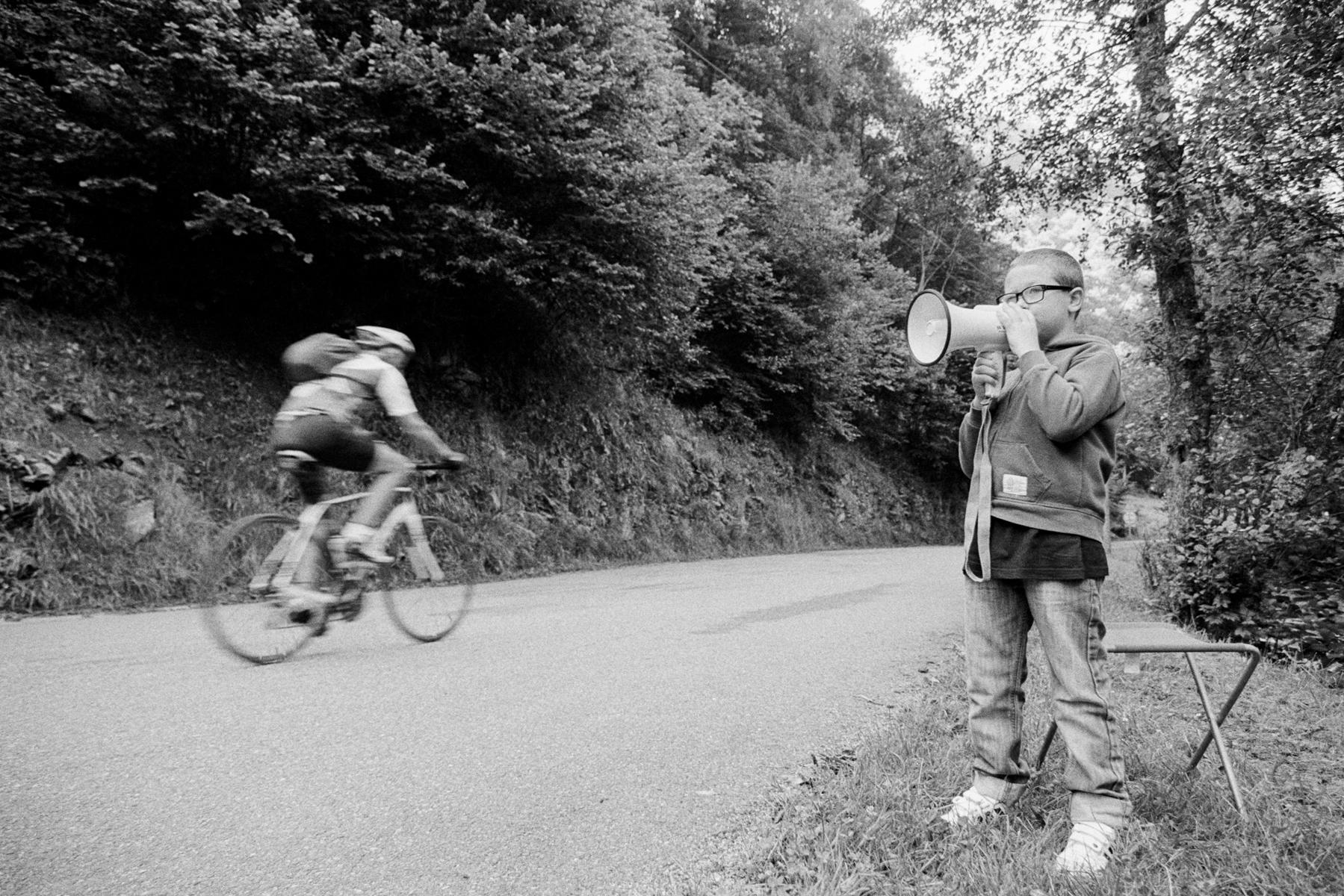 Le Tour de France 2014 This young fan is motivating every amateur with his megaphone who dares go up the climb at Port de Balès (1,755 m). Ce jeune amateur de vélo harangue de son mégaphone ceux qui tentent l'ascension vers Port de Balès (1.755m). Dieser kleine Fan feuert mit seinem Megafon jeden Amateur an, der den Aufstieg auf den Port de Balès wagt (1.755 m). Este pequeño aficionado con su megáfono anima a todos los que se atreven a subir a Port de Bales (1.755 m).